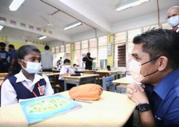 DR. RADZI jidin bertanyakan sesuatu kepada seorang murid Sekolah Kebangsaan Tengku Zainun yang kembali ke sekolah, semalam.