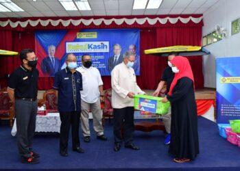 MUSTAPA Mohamed menyampaikan sumbangan bakul makanan kepada penerima pada Program Bakul Kasih AIM, Cawangan Jeli, Kelantan, hari ini. - UTUSAN ROSALWANI CHE SOH