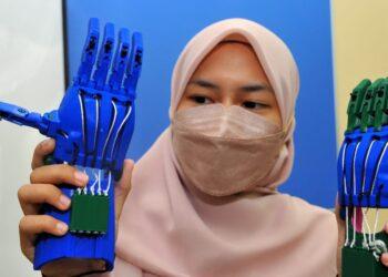 PELAJAR Kejuruteraan Bioperubatan, Amalina Has menunjukkan tangan 3D yang dihasilkan bagi tujuan membantu kanak-kanak Yaman yang mengalami kecacatan tangan pada majlis Serahan Tangan 3D ke Yaman di UTM, Johor Bahru. - UTUSAN/RAJA JAAFAR ALI