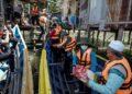 Anggota sukarelawan menyerahkan bantuan kepada penduduk Kuala Sungai Balung pada Misi Bantuan Kemanusiaan Sabah oleh Muslim Care Malaysia (MCM) bagi meringankan beban yang terjejas akibat wabak Covid-19 di Semporna , semalam. – MINGGUAN/FARIZ RUSADIO